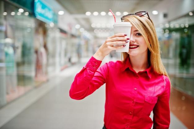 El retrato de una bella mujer vestida con una blusa roja, jeans casuales y tacones negros cubre la mitad de su rostro con una taza de café en un enorme centro comercial.