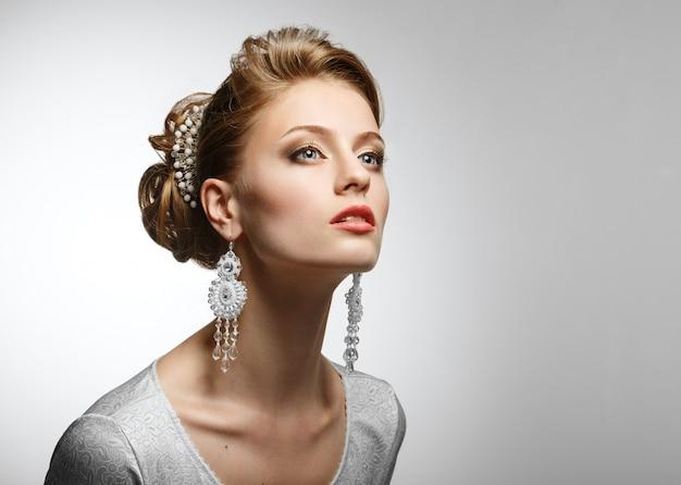 Retrato de una bella mujer con un vestido blanco y grandes aretes.