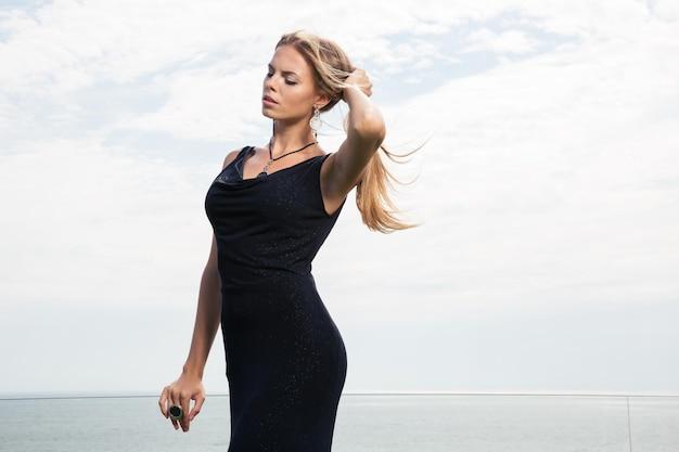 Retrato de una bella mujer en vestido negro posando con el mar en la pared