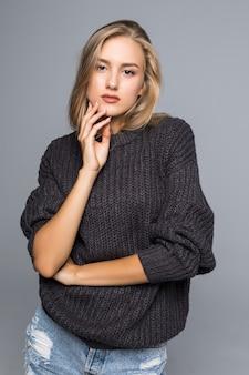 Retrato de una bella mujer vistiendo un suéter de punto cálido en su cuerpo sobre un fondo gris aislado