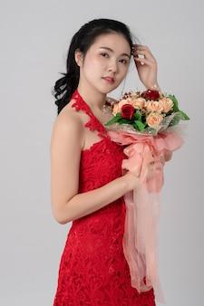 Retrato de bella novia asiática con vestido rojo con ramo de flores en manos sobre blanco