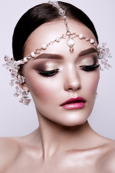 Retrato de una bella novia morena de moda, dulce y sensual. maquillaje de boda y cabello. ojos azules.