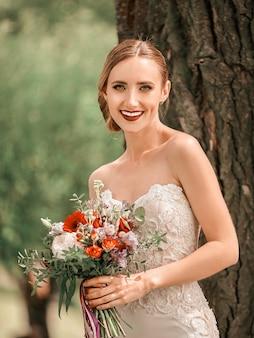 Retrato de una bella novia de pie cerca de un árbol en un parque de la ciudad