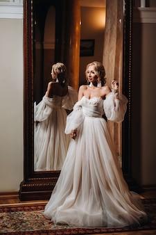 Retrato de una bella novia de pie de espaldas al espejo.