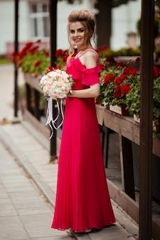 Retrato de una bella novia con un ramo de novia. chica rubia con cabello rizado y maquillaje de moda.