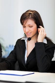 Retrato de una bella representante del cliente en el trabajo