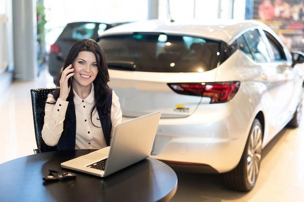 Retrato de bella smilling agente de seguros sentado y hablando por teléfono cerca de un auto nuevo