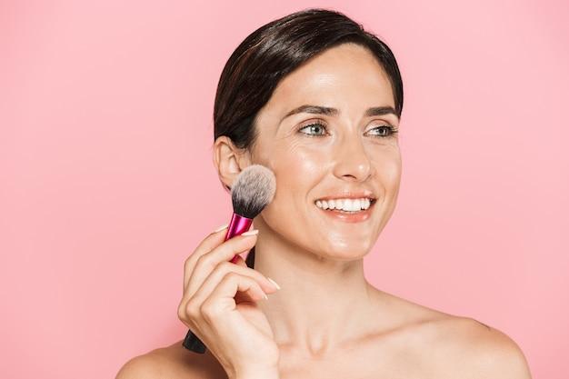 Retrato de belleza de una atractiva joven sonriente en topless que se encuentran aisladas sobre la pared rosa, sosteniendo el pincel de maquillaje