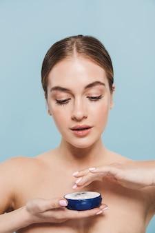 Retrato de belleza de una atractiva joven en topless aislada sobre pared azul, aplicando crema de un recipiente