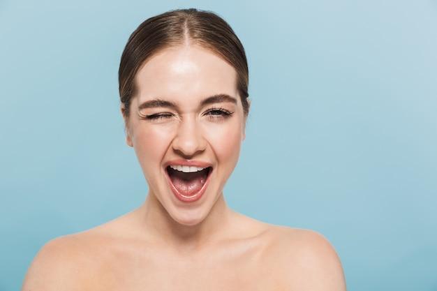Retrato de belleza de una atractiva joven en topless aislada sobre pared azul, guiñando un ojo