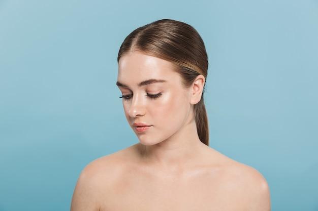 Retrato de belleza de una atractiva joven en topless aislada sobre pared azul, mirando a otro lado
