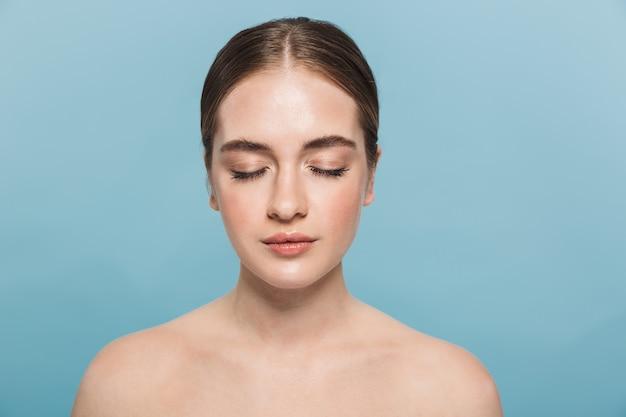 Retrato de belleza de una atractiva joven en topless aislada sobre pared azul, ojos cerrados