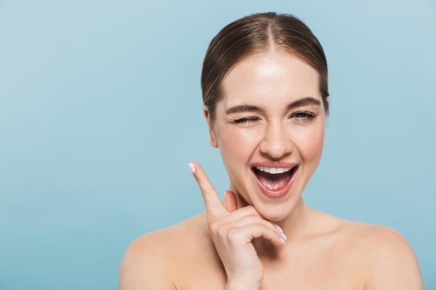 Retrato de belleza de una atractiva joven en topless aislada sobre pared azul, posando
