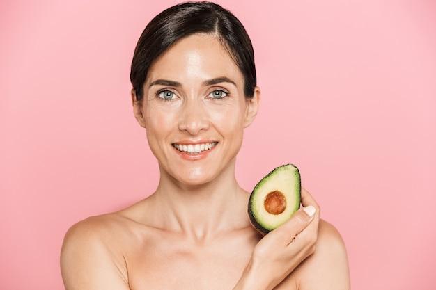 Retrato de belleza de una atractiva mujer morena en topless saludable sonriente aislada, mostrando aguacate en rodajas