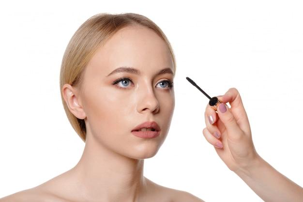 Retrato de la belleza de una bella mujer desnuda mitad sonriente posando con pinceles de maquillaje