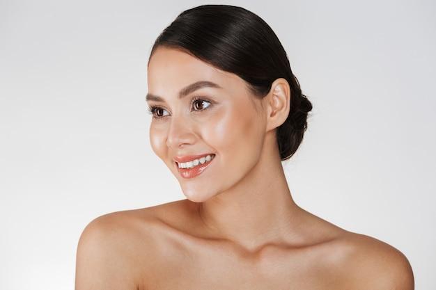 Retrato de belleza de feliz dama elegante con cabello castaño en moño sonriendo y mirando a un lado, aislado en blanco