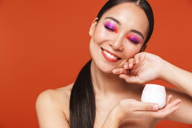 Retrato de belleza de una feliz joven mujer asiática en topless con cabello morena con maquillaje brillante, de pie aislado en rojo, mostrando la botella con crema facial