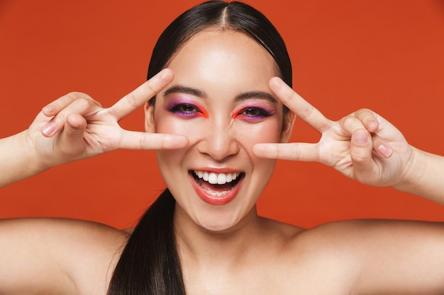 Retrato de belleza de una feliz joven mujer asiática en topless con cabello morena con maquillaje brillante, de pie aislado en rojo, mostrando gesto de paz