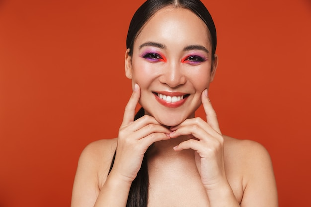Retrato de la belleza de una feliz joven mujer asiática en topless con cabello morena con maquillaje brillante, que se encuentran aisladas en rojo
