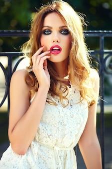 Retrato de belleza glamour de hermosa sensual modelo caucásica joven con maquillaje de noche en vestido blanco de verano posando en la calle