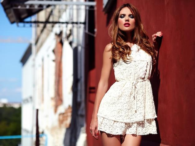 Retrato de belleza glamour de hermosa sensual modelo caucásica joven con maquillaje de noche en vestido blanco de verano posando en el fondo de la calle cerca de la pared roja