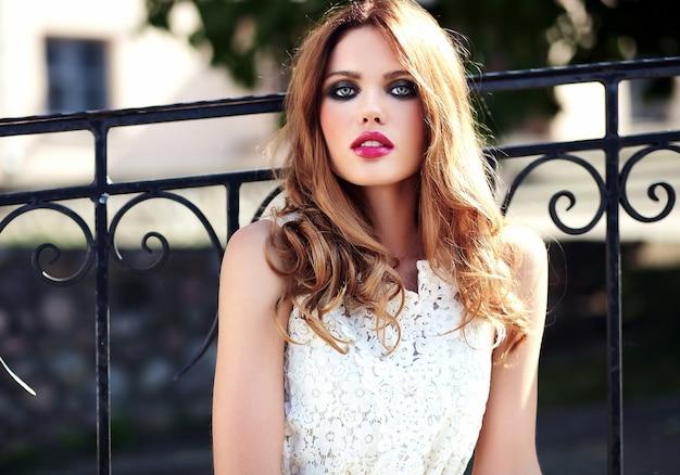 Retrato de belleza glamour de hermosa sensual modelo caucásica joven con maquillaje de noche en vestido de verano blanco posando en el fondo de la calle