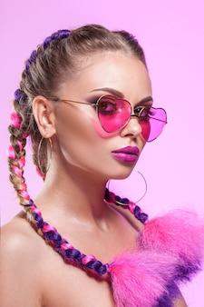 Retrato de belleza de glamour de una niña. maquillaje brillante, lentes color de rosa, trenzas, peinado con coletas