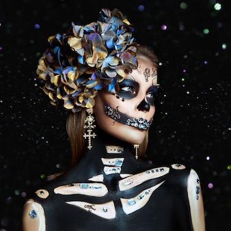 Retrato de belleza de halloween de una mujer esqueleto de muerte brillo de bokeh, el maquillaje en la cara. disfraz de halloween de la muerte de niña. dia de los muertos. encantadora y peligrosa calavera catrina