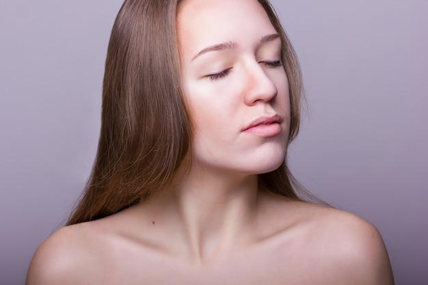 Retrato de belleza de una hermosa joven sin maquillaje y cabello castaño