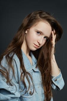 Retrato de la belleza de una hermosa joven en una pared oscura. cosméticos para adolescentes, tratamiento del acné.