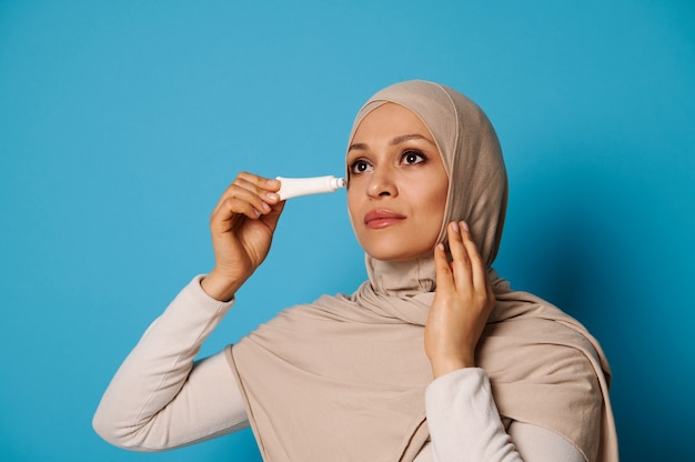 Retrato de belleza de hermosa mujer árabe con piel perfecta aplicando crema debajo de los ojos aislados