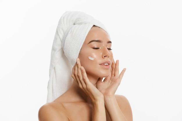 Retrato de belleza de una hermosa mujer desnuda mitad sonriente con una toalla en su cabello aplicar crema
