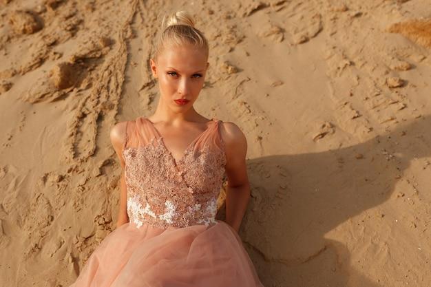 Retrato de belleza. hermosa mujer rubia posando en vestido bordado en el desierto, tumbado en la arena. foto de verano. luz del atardecer.