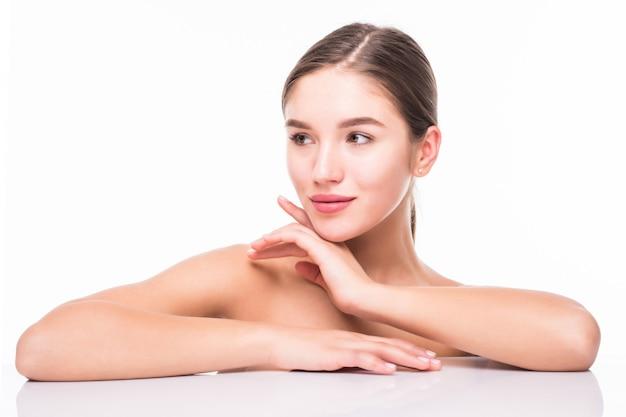 Retrato de belleza de una joven atractiva mujer semidesnuda con piel perfecta posando y mirando a otro lado sobre la pared blanca