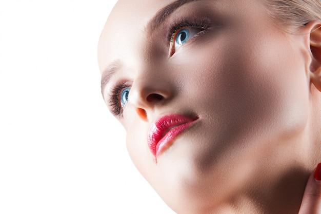 Retrato de belleza joven y bella mujer rubia atractiva mujer en blanco señora demuestra maquillaje