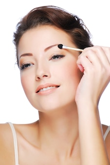 Retrato de belleza joven mujer caucásica aplicar sombra de ojos con aplicador cosmético