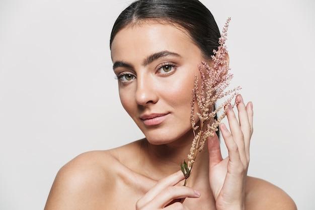 Retrato de belleza de una joven mujer morena atractiva sana que se encuentran aisladas sosteniendo la planta de flores cerca de su cara