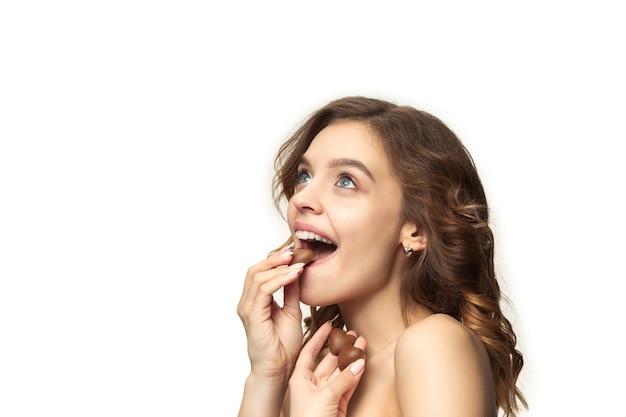 Retrato de belleza de una linda chica en acto de comer un caramelo de chocolate sobre una pared blanca.