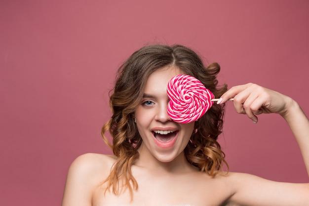 Retrato de belleza de una linda chica en acto para comer un caramelo sobre pared rosa