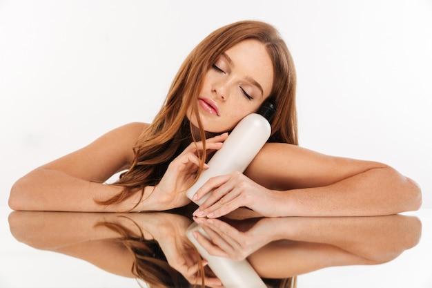 Retrato de belleza de misteriosa mujer de jengibre con el pelo largo sentada junto a la mesa del espejo con una botella de loción