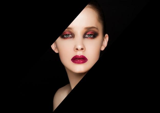 Retrato de belleza modelo de maquillaje de ojos y labios rojos sobre fondo negro