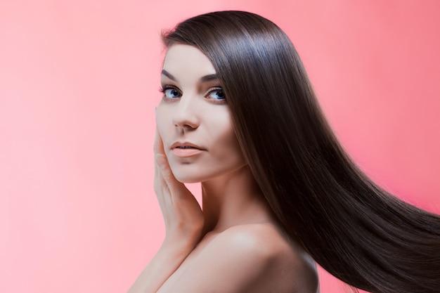 Retrato de belleza de morena con cabello perfecto, en una pared de color rosa. cuidado del cabello