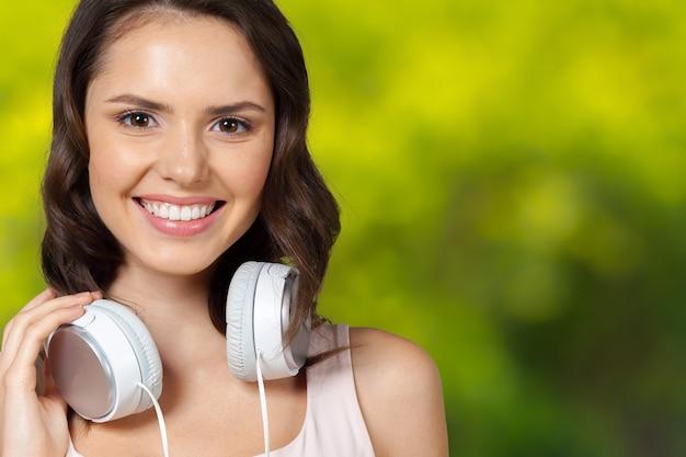 Retrato de belleza morena escuchando música en auriculares blancos