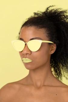 Retrato de belleza de mujer afro con brillo de labios amarillo y gafas de sol