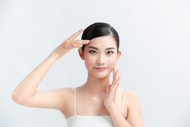 Retrato de belleza de mujer asiática joven en pared blanca
