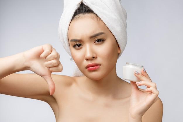 Retrato de la belleza de la mujer asiática semidesnuda que mira en cámara y que sostiene la crema de cara