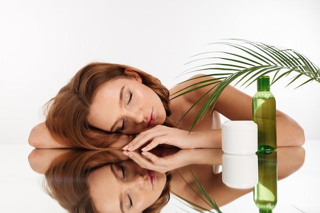 Retrato de belleza de mujer atractiva de jengibre con el pelo largo acostado en la mesa de espejo con los ojos cerrados cerca de la botella de loción