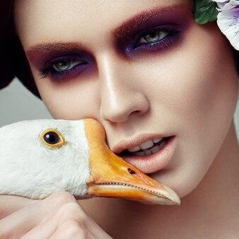 Retrato de belleza de una mujer atractiva con maquillaje que sostiene un drake