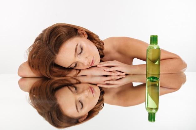 Retrato de belleza de mujer bonita de jengibre con el pelo largo acostado en la mesa de espejo con los ojos cerrados cerca de la botella de loción