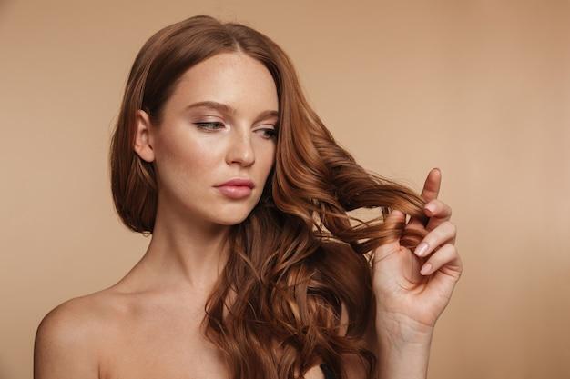 Retrato de belleza de mujer bonita de jengibre con el pelo largo tocando su pelo y mirando a otro lado